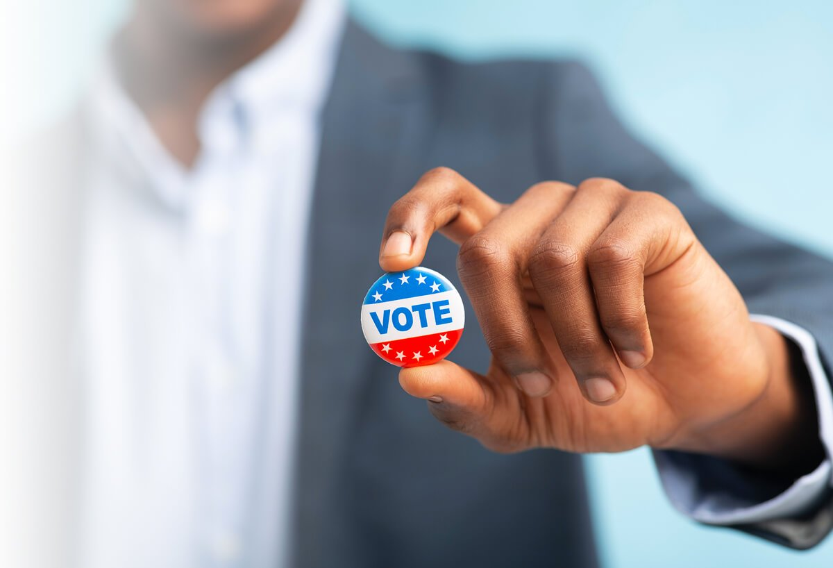 A man holding a Vote pin